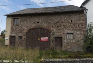 Eine alte Scheune mit Baustellenschild in Niederbettingen