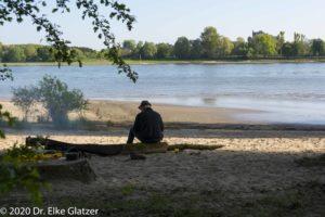 Am Rodenkirchener Rheinufer sitzt ein Mann mit dem Rücken zum Fotografen